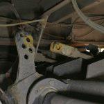 Schwertransport-Fahrer schraubt Bremsgestänge für Fahrt bis nach Moskau ab